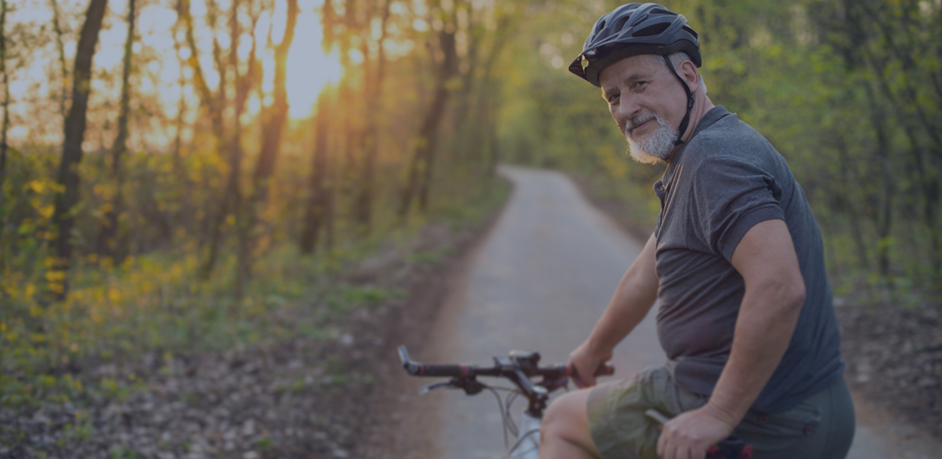 senior man riding on a bike trail and looking back