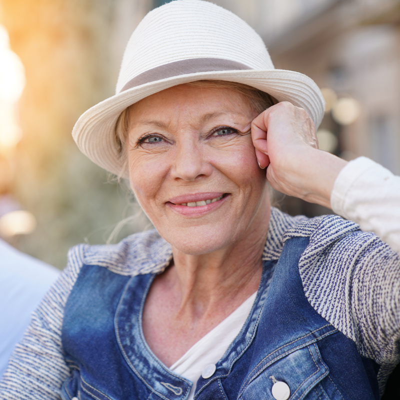 happy senior woman wearing a hat and sitting outside