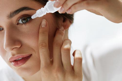 woman applying eye drops