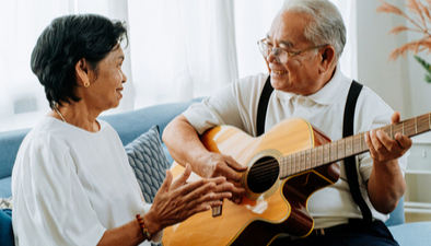 senior man playing guitar for his wife